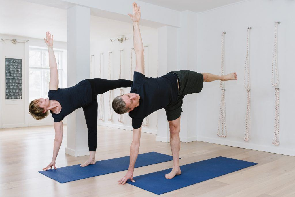 a man and a woman practising yoga on blue mats